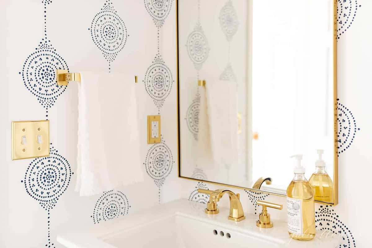 A modern bathroom with a navy light fixture and navy and white patterned wallpaper, brass faucet on pedestal sink