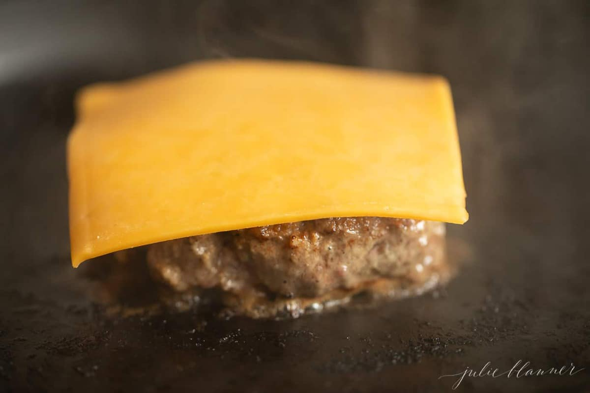 A burger on the stove in a cast iron pan, slice of cheese on top before it melts.