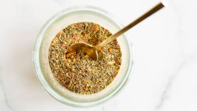 A clear glass jar of italian seasoning blend, gold spoon sticking out.