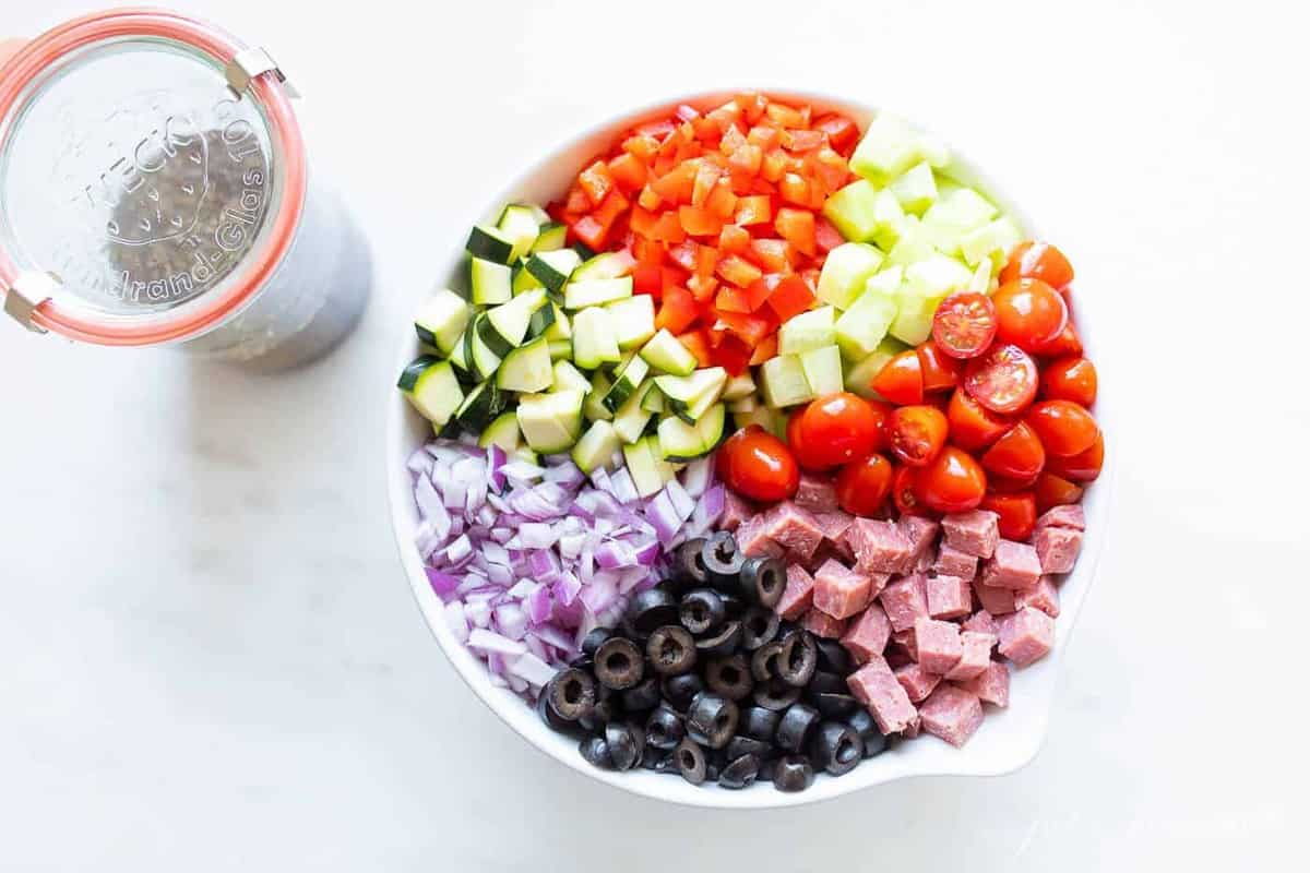 A white bowl filled with ingredients for a homemade spaghetti salad recipe.