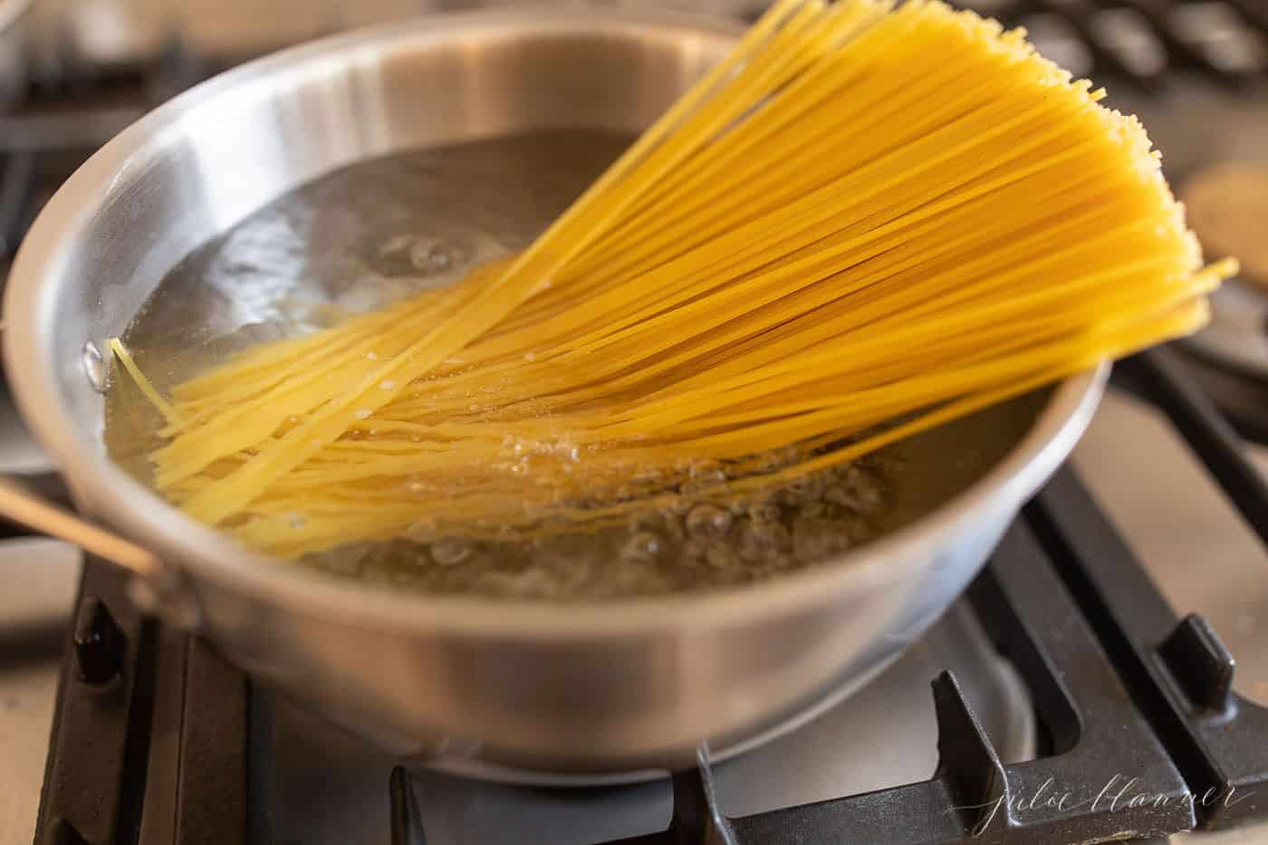 A bowl of boiling water on a stove top, spaghetti noodles halfway in the water and half out.