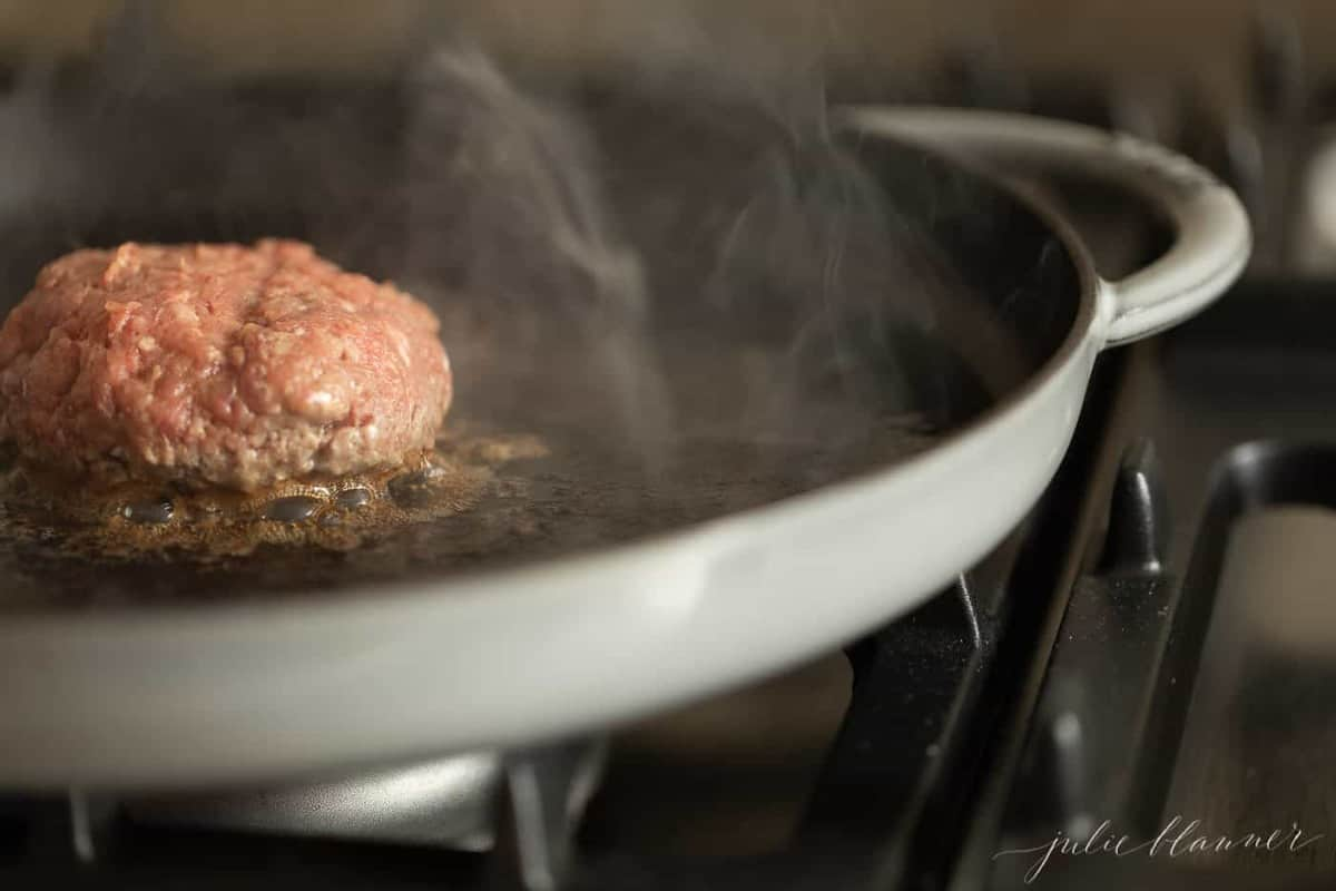 A burger being cooked in a cast iron pan.