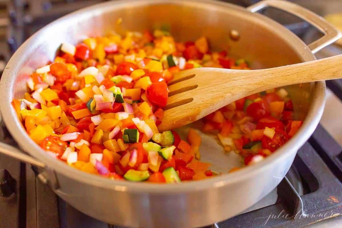 fresh veggies piled into a silver stockpot to go into a veggie pasta salad.