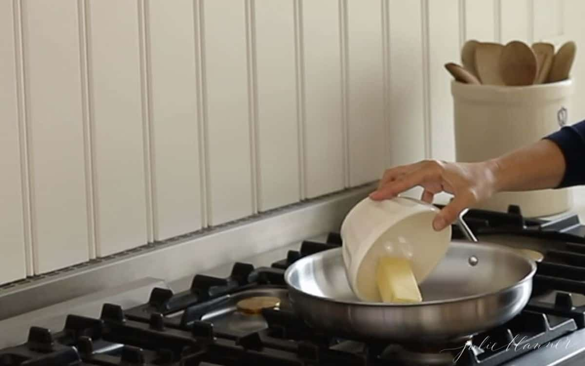 Hands placing a stick of butter into a silver pan on a stove.