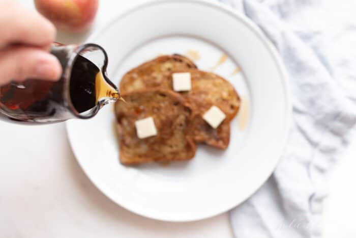 A white plate with slices of apple fritter french bread, syrup pouring over the top.
