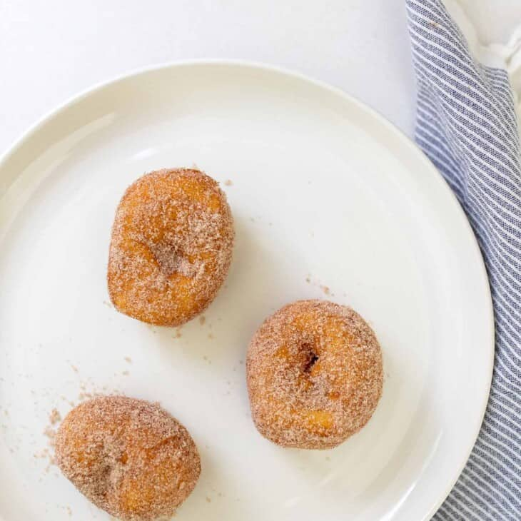 A white plate with three biscuit donuts covered in cinnamon sugar.