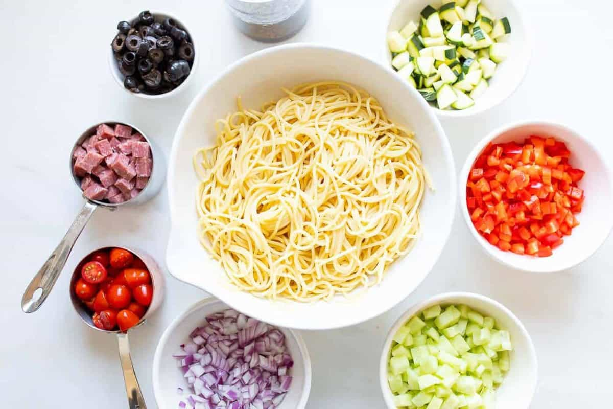 A large white bowl of cooked spaghetti surrounded by small bowls of ingredients to make a spaghetti salad recipe.