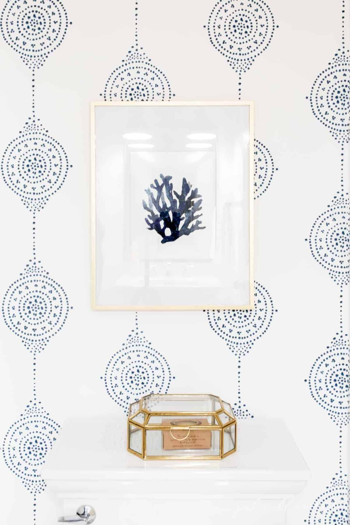 Blue and white patterned bathroom wallpaper with seashell art over the toilet.