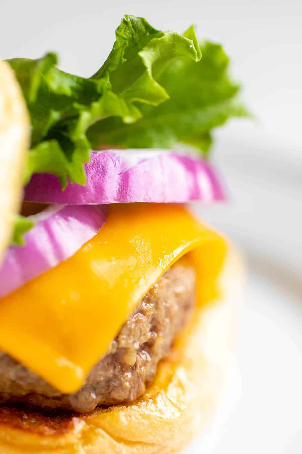 A close up shot of a cast iron burger stacked with lettuce, red onions and cheese.
