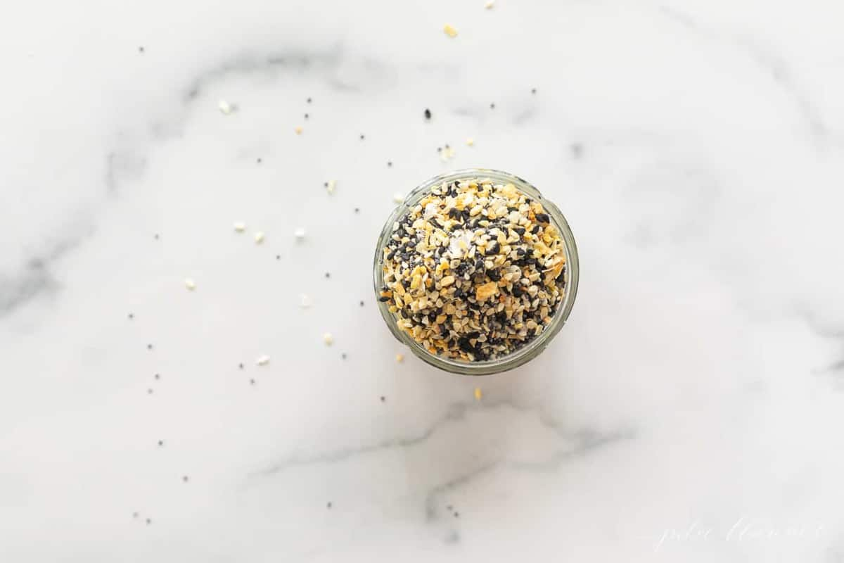 A clear glass jar on a marble surface, filled with everything bagel seasoning.