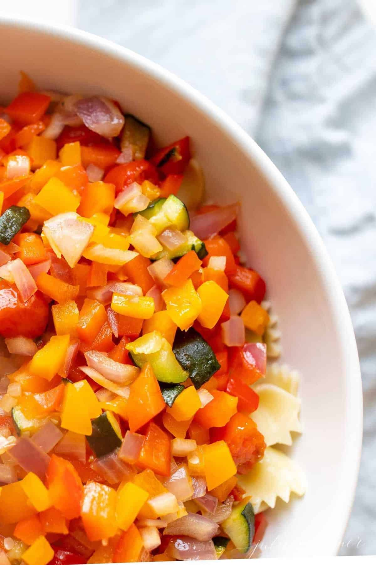 A white bowl filled with veggie pasta salad.