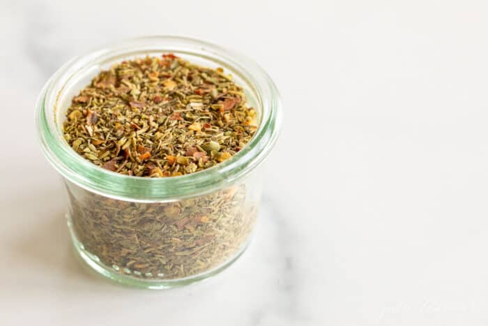 A clear glass jar of italian seasoning blend.