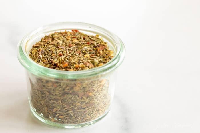 A clear glass jar of italian seasoning blend.