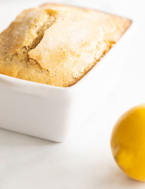 A marble counter top background with a small loaf of lemon poppy seed bread recipe, lemon to the side.