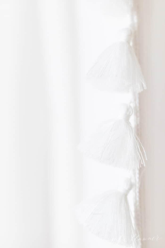A white tasseled shower curtain in a bathroom update.