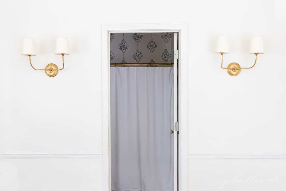 A white painted hallway with two gold wall sconces, door open into bathroom in between.