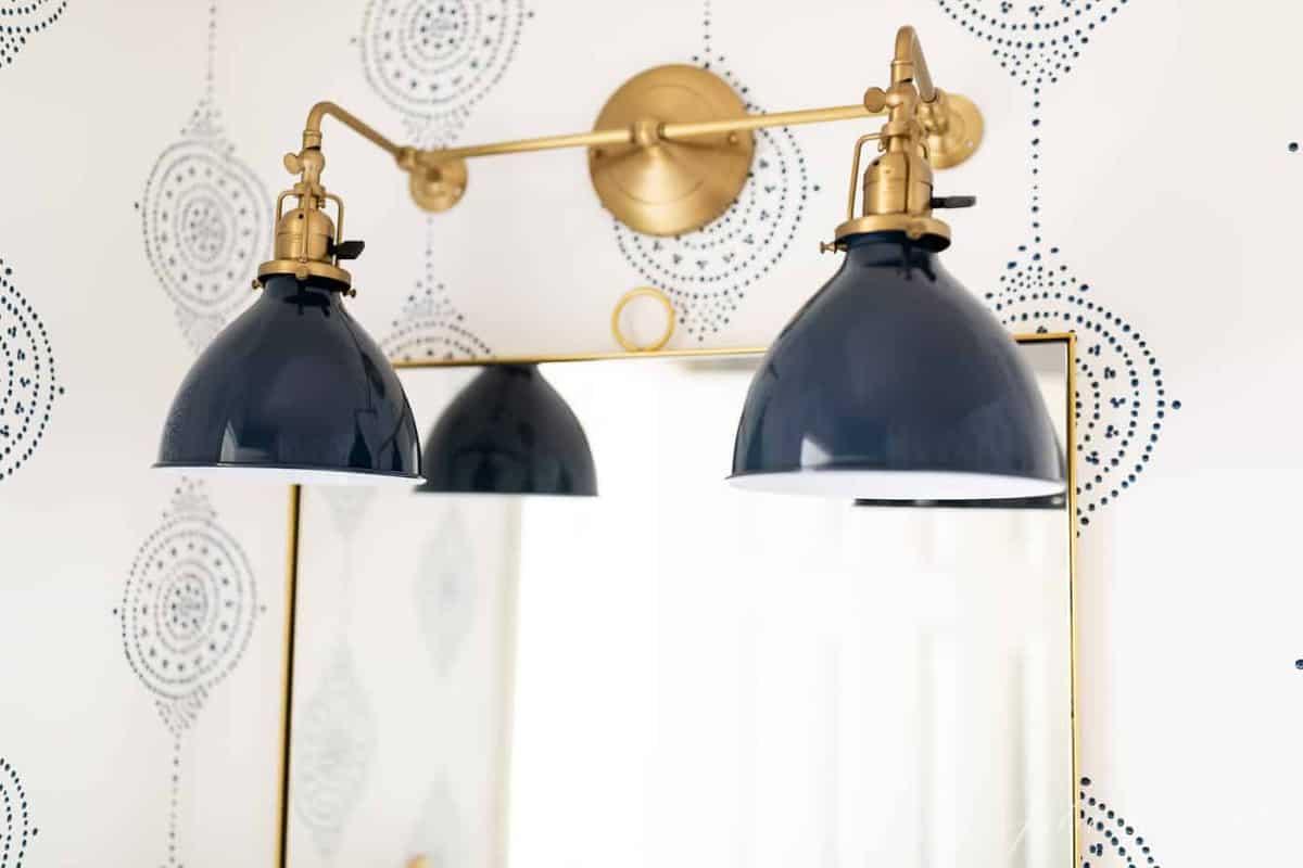 A navy and brass bathroom light fixture in a modern bathroom idea refresh.