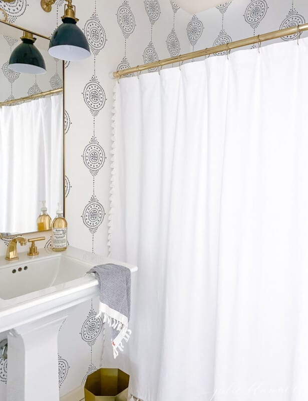 A modern bathroom with a navy light fixture and navy and white patterned bathroom wallpaper.