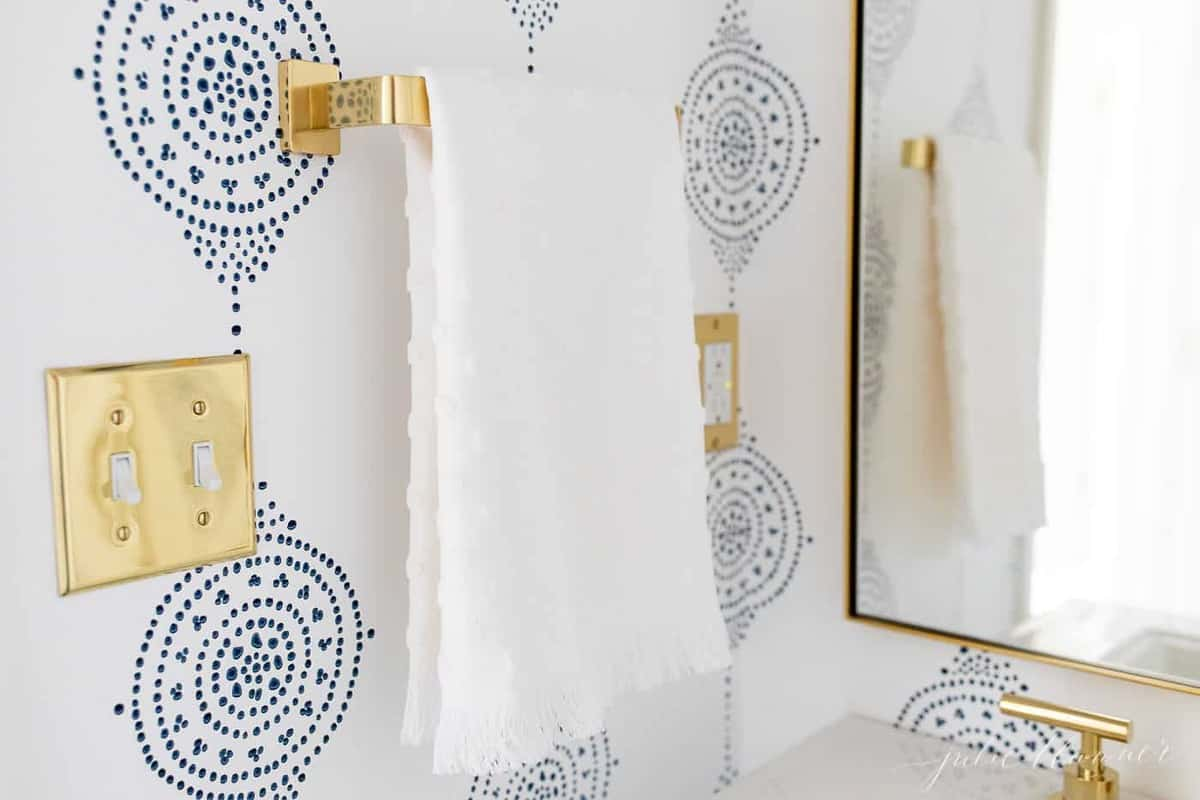 A blue and white walppapered bathroom with a gold towel bar.