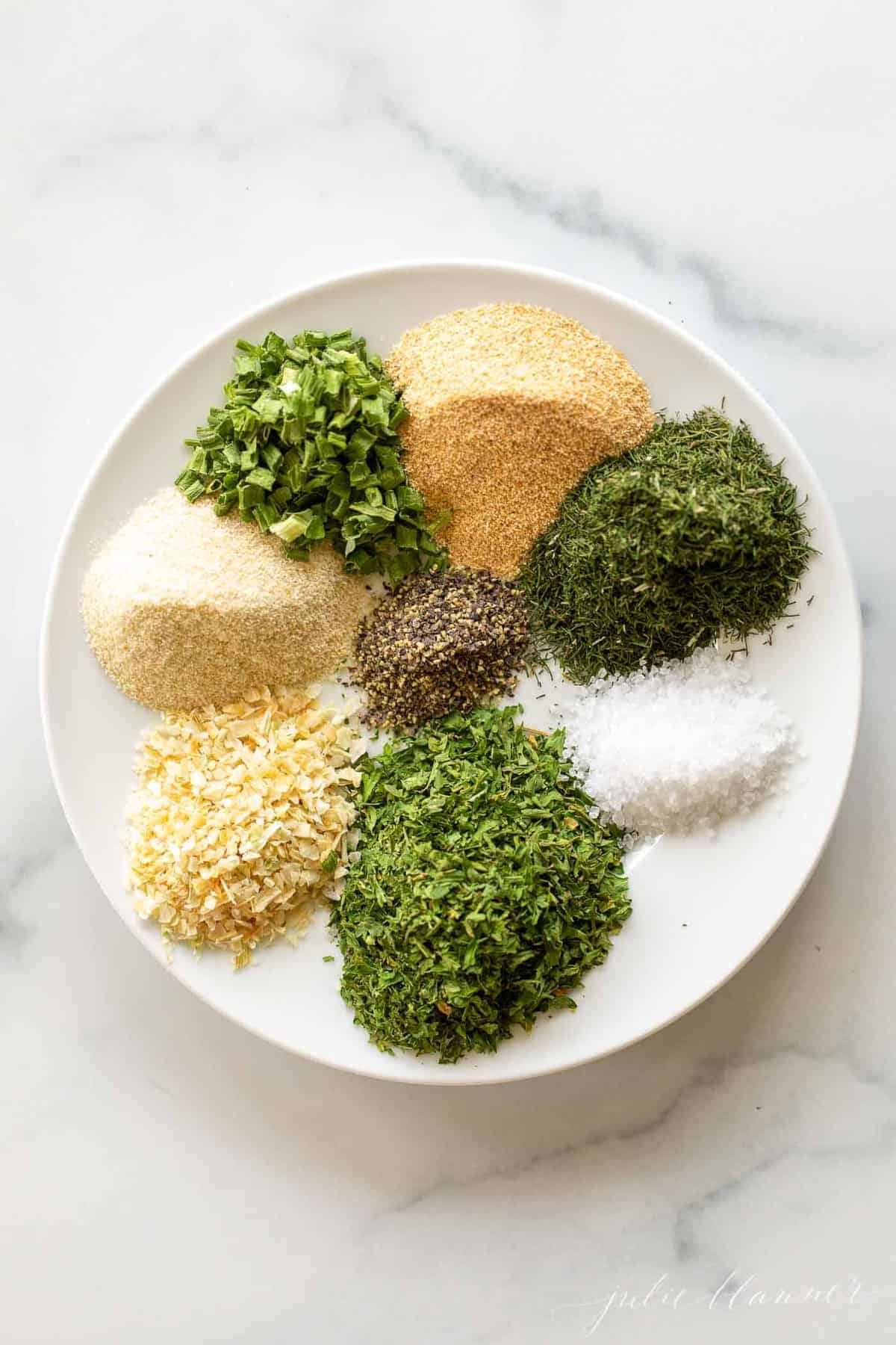 spices and herbs on a white plate on marble background