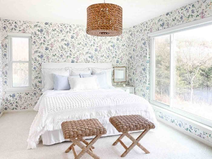 wallpapered bedroom with white bedding rattan stools