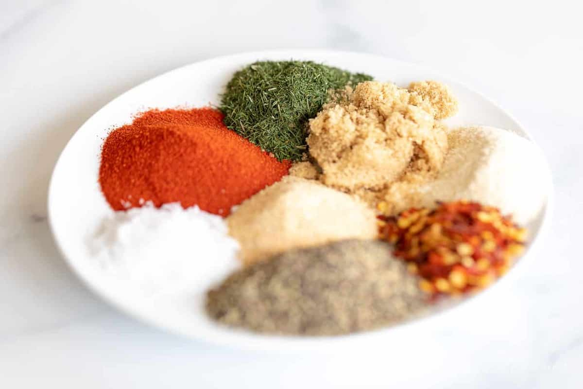 A white plate full of individual piles of seasonings and spices for a steak seasoning recipe blend.