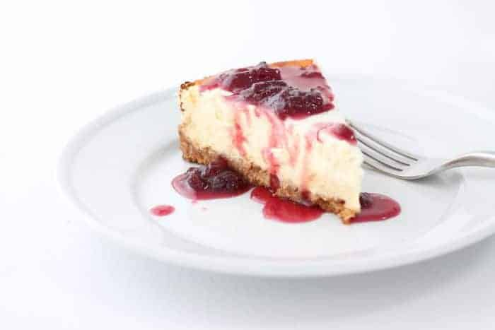 A white background and white place with a slice of cheesecake drizzled with a strawberry topping for cheesecake.