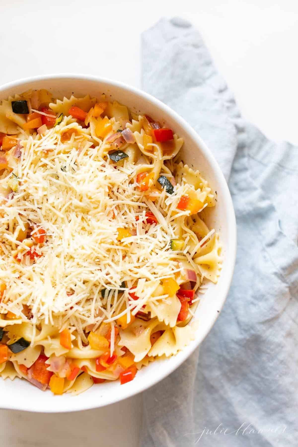A white bowl filled with a fresh vegetarian pasta salad topped with Parmesan cheese.