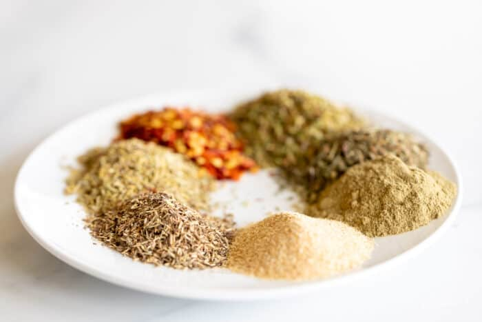 A white plate full of piles of italian herbs and spices.