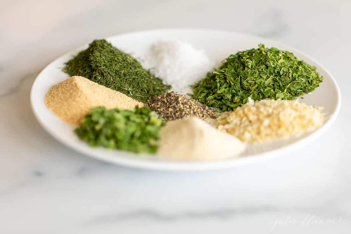 ranch herbs and spices on white plate on marble counter