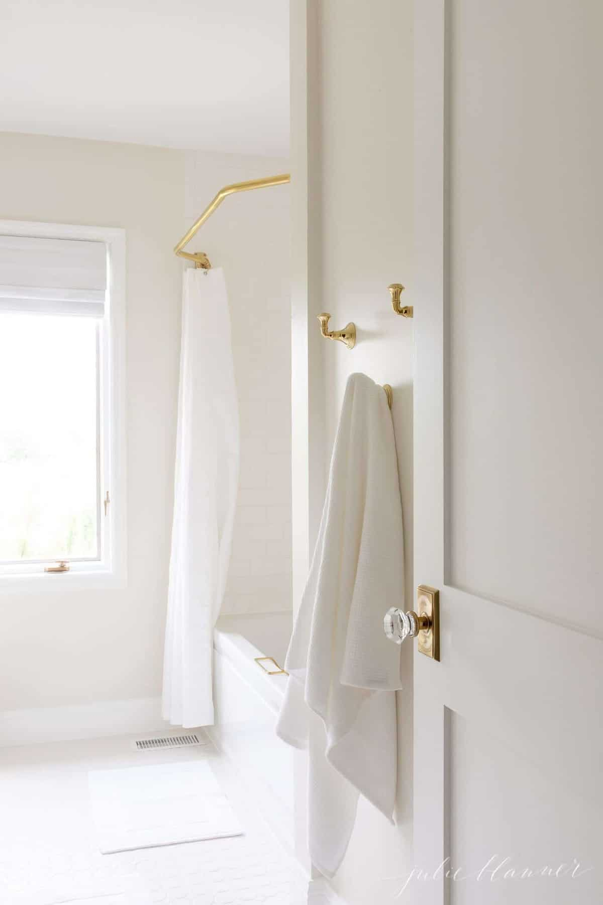 Looking into a white bathroom that uses Benjamin Moore White Dove for trim paint.