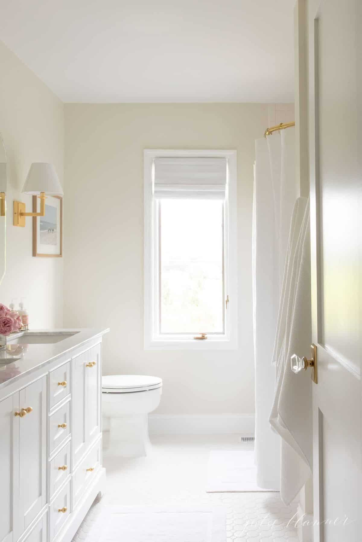A pretty white bathroom with Benjamin Moore White Dove trim paint.