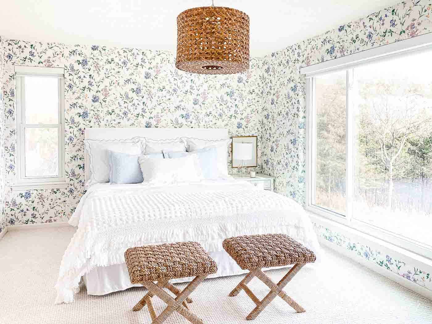 wallpapered bedroom with white slipcovered headboard, white bedding and rattan stools