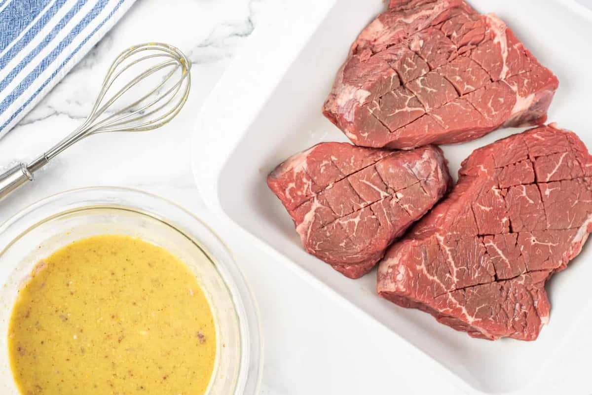 A dish with raw steak, bowl of steak marinade recipe to the side.