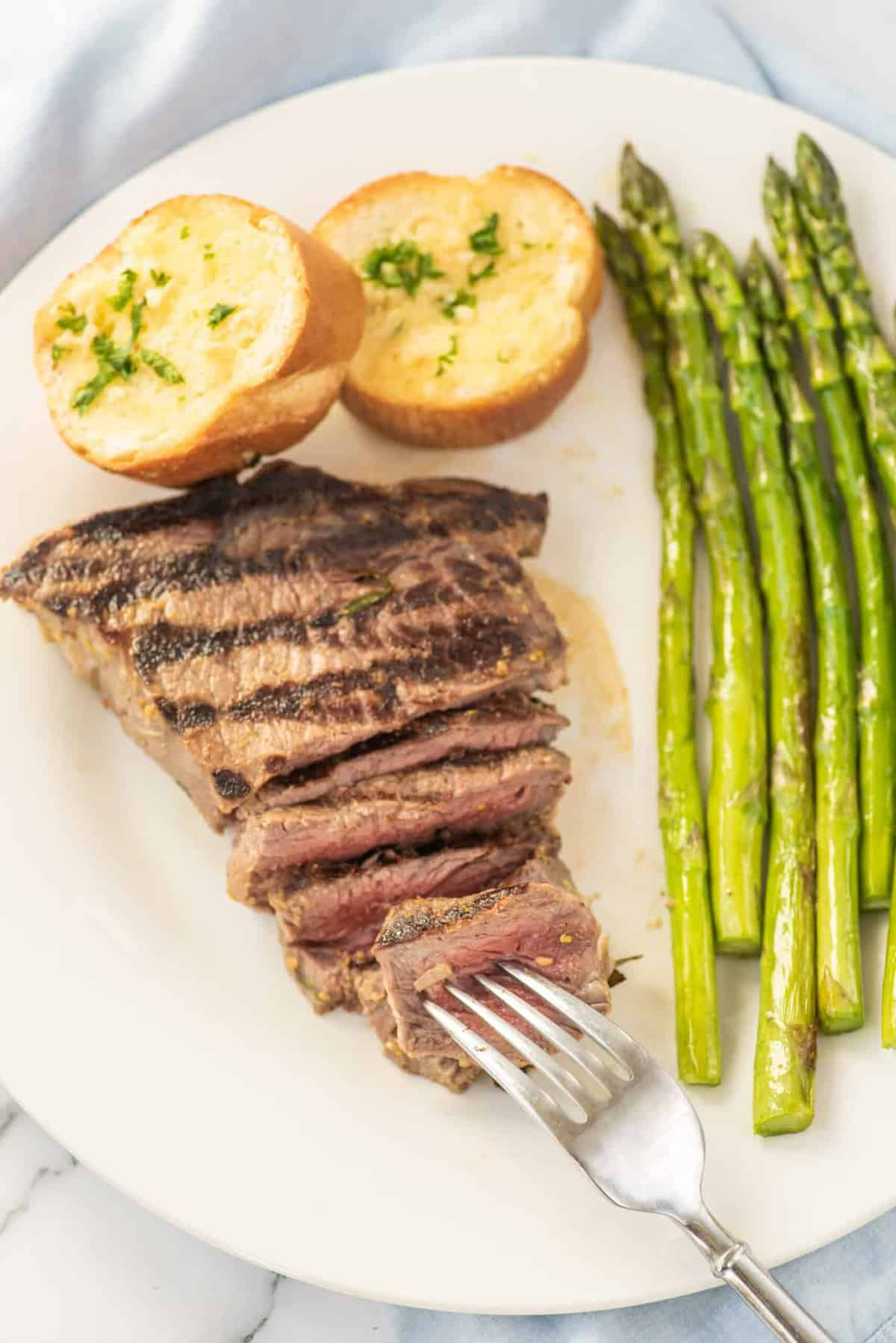 A grilled steak with a side of asparagus on a white plate.