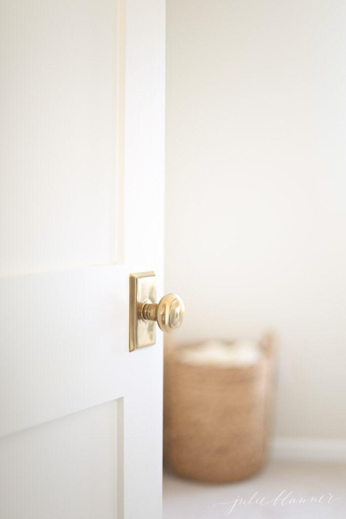 White hallway door with brass knob, looking into bedroom.