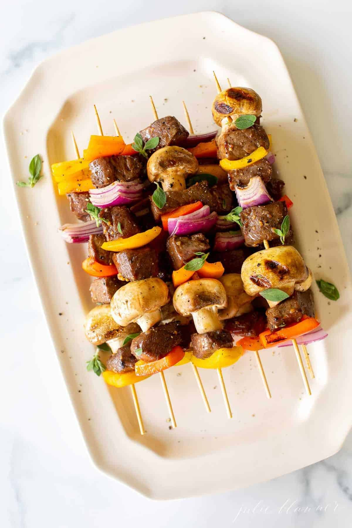 A white platter filled with grilled steak kabobs.