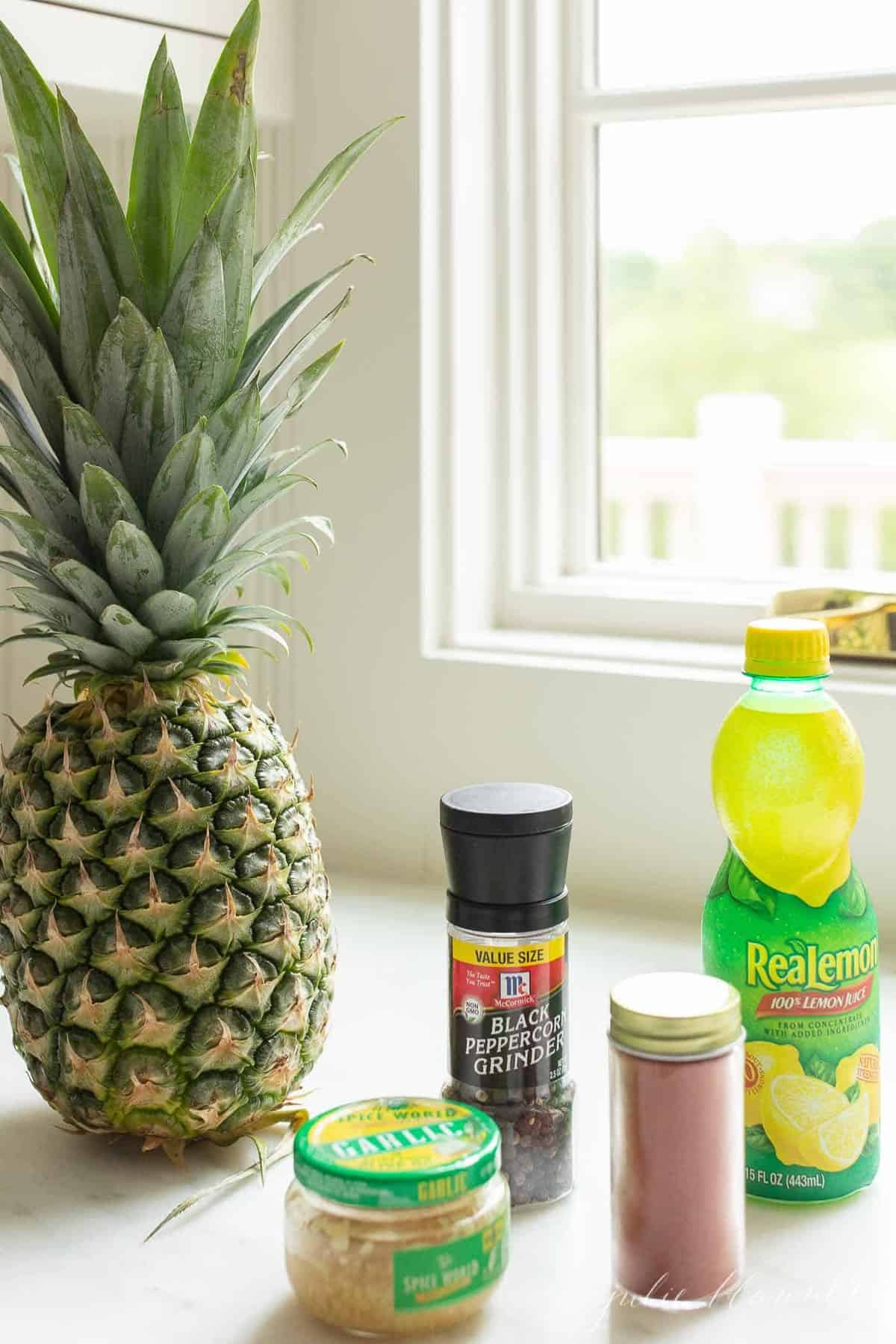 A kitchen counter with ingredients for a chicken kabob marinade, whole pineapple to the side.
