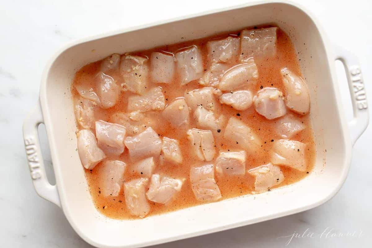 A white dish filled with chicken marinating in a chicken kabob marinade.