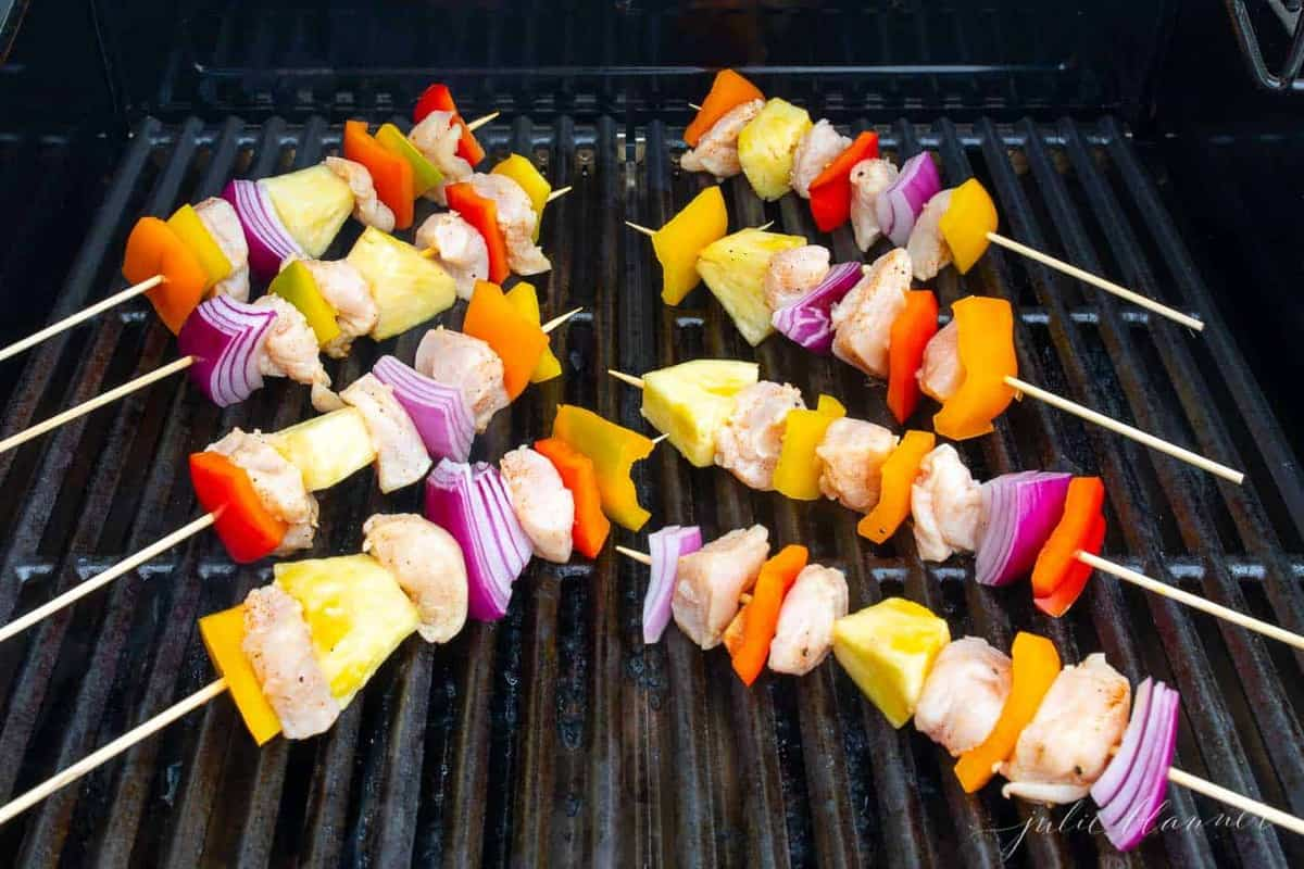 Colorful chicken kabobs cooking on a grill.