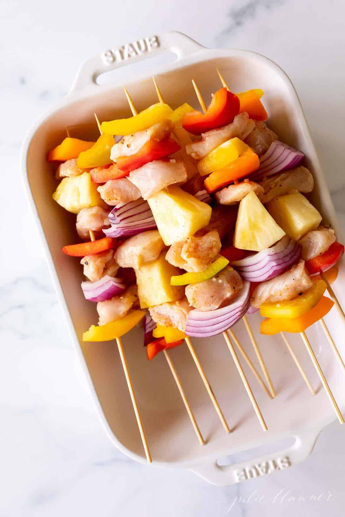 A white baking dish filled with bamboo chicken skewers, on a marble surface.