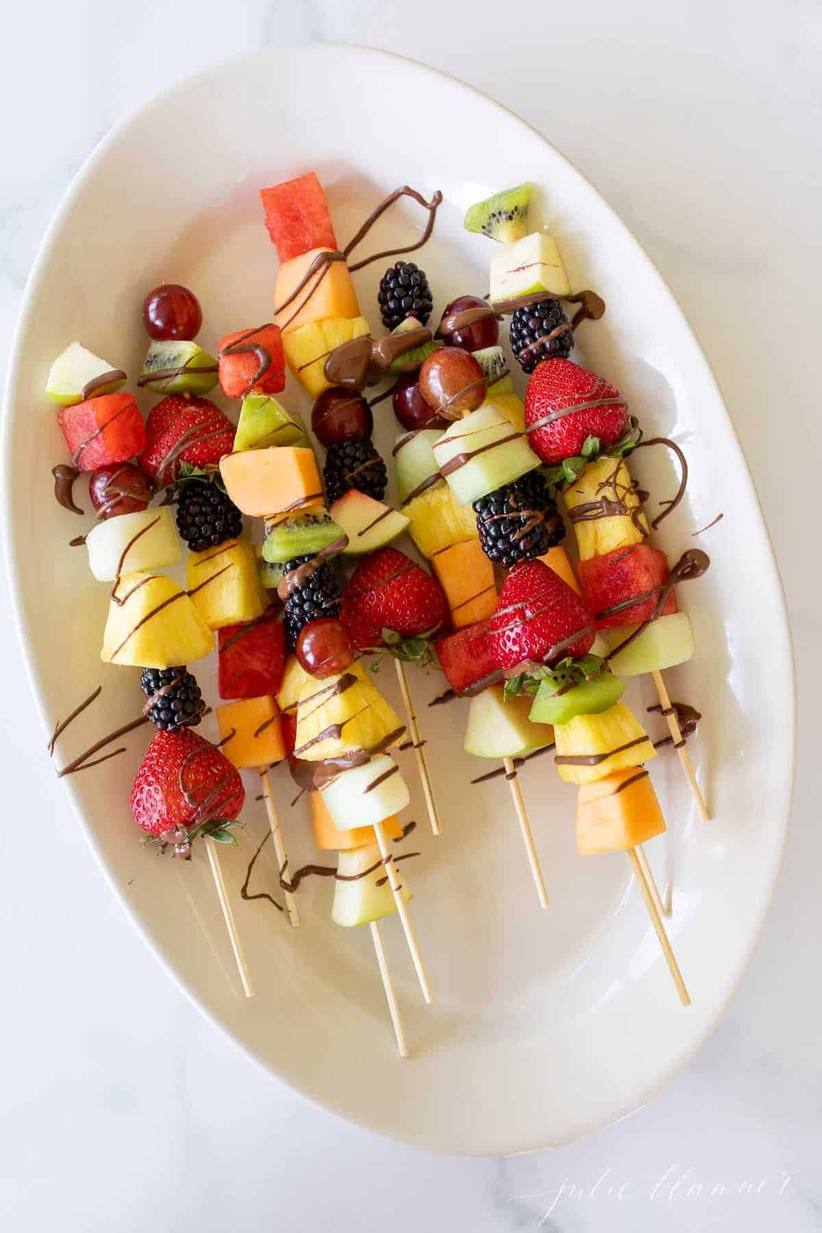 Colorful fruit skewers on a white oval platter, covered in a drizzle of chocolate.