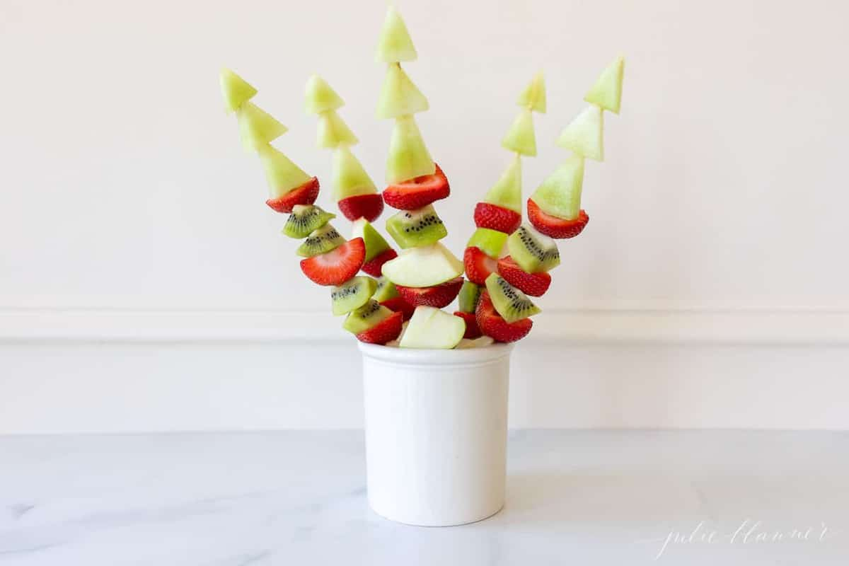 Marble surface with a white canister filled with fresh fruit skewers.