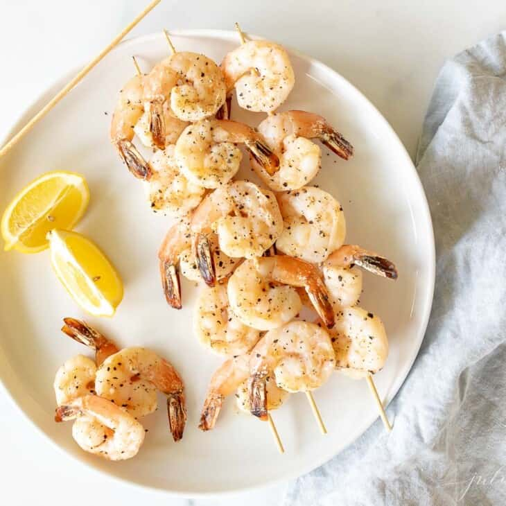 A white plate with skewers of lemon garlic shrimp kabobs.