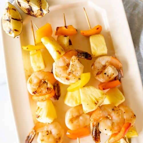 A white platter filled with pineapple shrimp skewers.