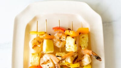 Pineapple shrimp skewers recipe on a white platter.