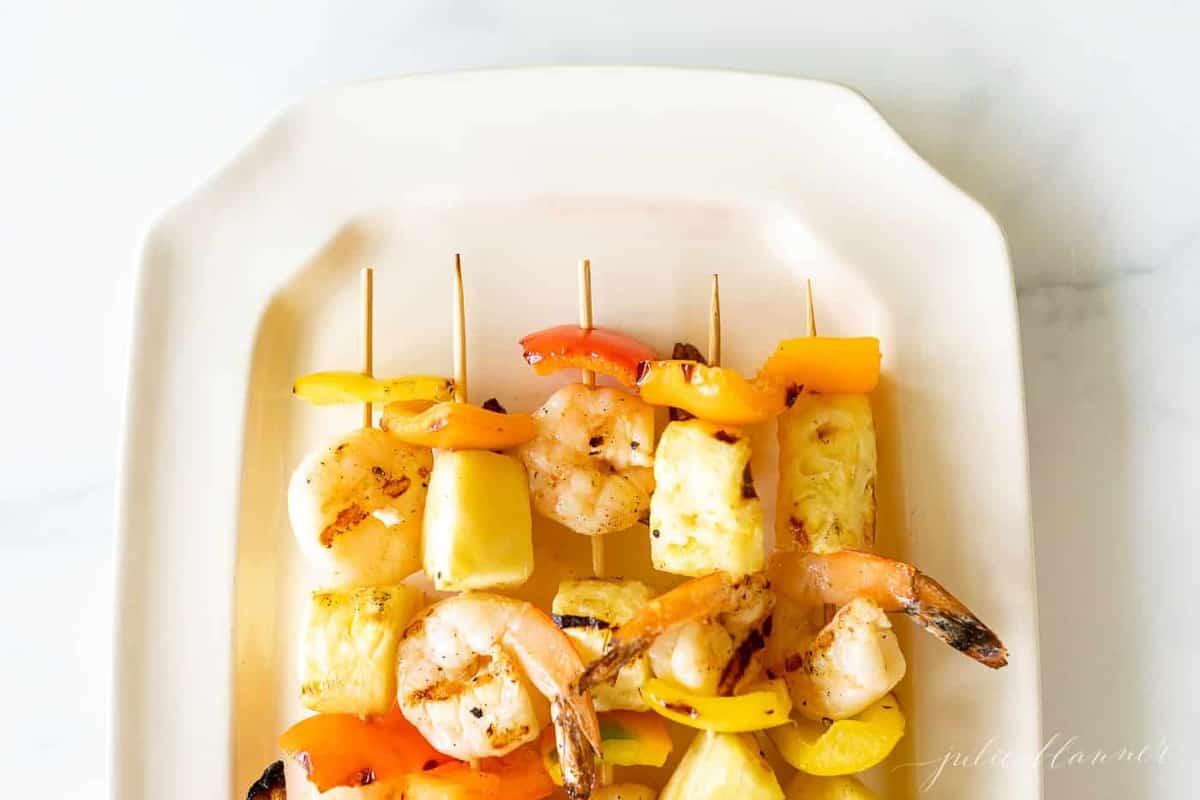 Pineapple shrimp skewers recipe on a white platter.