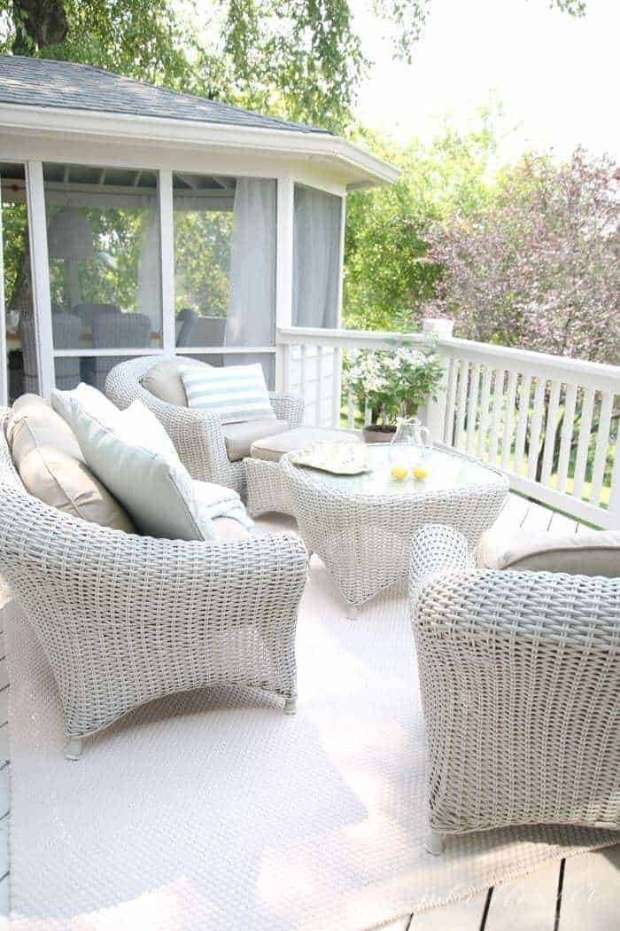 A painted white deck with wicker furniture.