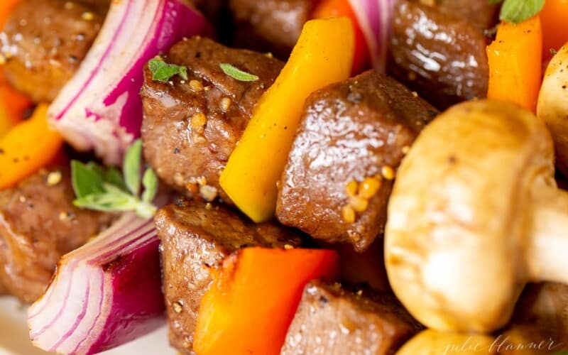 A close up image of steak kabobs on a white platter.