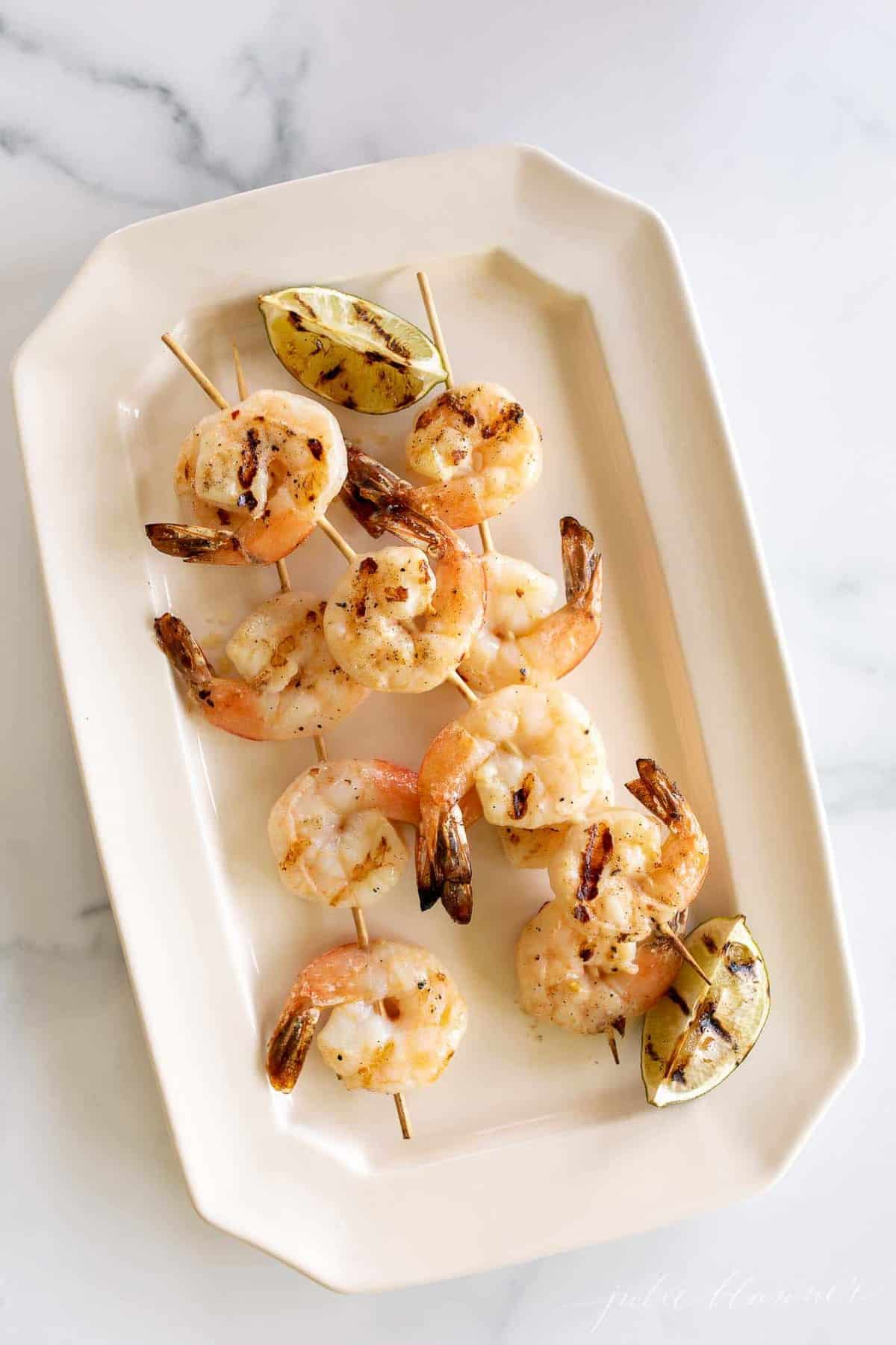 A white platter filled with grilled shrimp skewers.